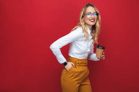 Smiling beautiful young blonde woman standing isolated over red background, holding takeaway coffee cup Фото со стока