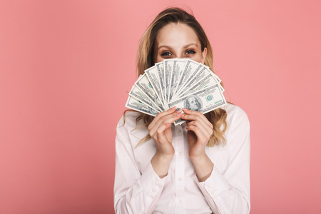 Portrait of stylish woman 30s in trendy wear hiding while holding money fan isolated over pink background Stock fotó