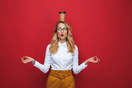 Beautiful funny young blonde woman standing isolated over red background, balancing, holding coffee cup Фото со стока