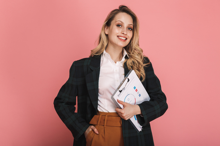 Photo of happy businesswoman wearing jacket holding clipboard with chart isolated over pink background