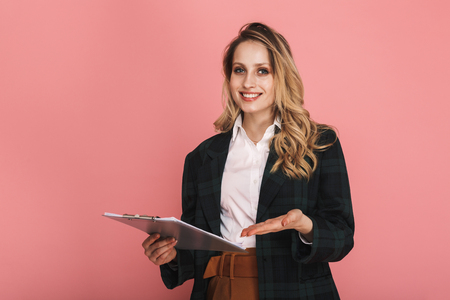 Photo of caucasian businesswoman wearing jacket holding clipboard with chart isolated over pink background Stock Photo