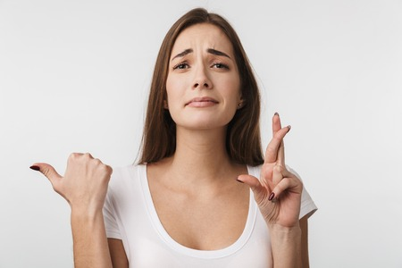 Attractive young woman standing isolated over white background, holding fingers crossed for good luck Banco de Imagens