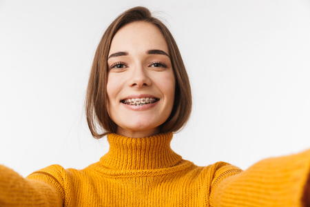 Lovely young girl wearing braces standing isolated over white background, taking a selfie