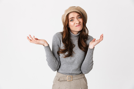 Portrait of discontent woman 30s wearing hat shrugging and throwing up hands with helplessness isolated over white background