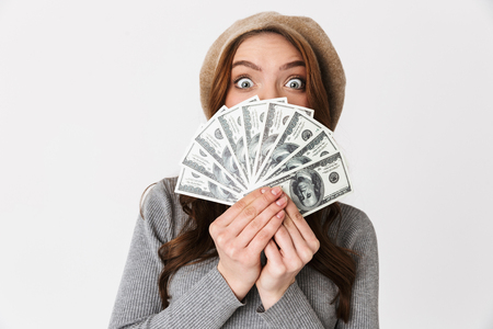 Image of shocked beautiful woman holding money isolated over white wall background. Stock Photo