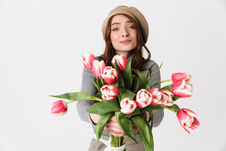 Photo of positive woman 30s wearing hat holding bunch of beautiful flowers isolated over white background