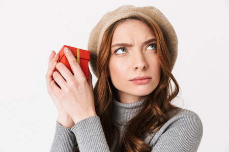 Photo of concentrated woman 30s wearing hat holding red gift box isolated over white background