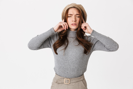 Annoyed young woman standing isolated over white background, cover ears
