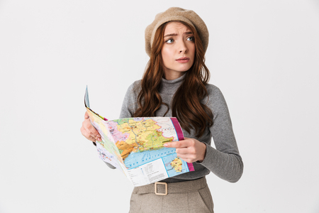 Photo of puzzled woman 30s wearing hat holding and reading world map isolated over white background
