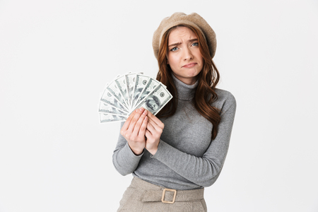 Photo of frowning woman 30s wearing hat holding fan of dollar money isolated over white background