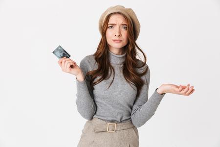 Imagen de mujer hermosa confundida con tarjeta de crédito aislada sobre fondo de pared blanca. Foto de archivo