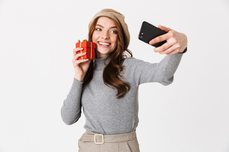 Photo of european woman 30s wearing hat taking selfie on cell phone while holding red gift box isolated over white background