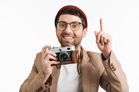 Photo of cheerful man 30s wearing hipster hat rejoicing while holding and photographing on retro camera isolated over white background Stock Photo