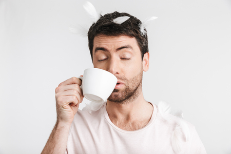 Image of attractive man 30s with bristle in casual t-shirt drinking coffee while standing under falling feathers isolated over white background