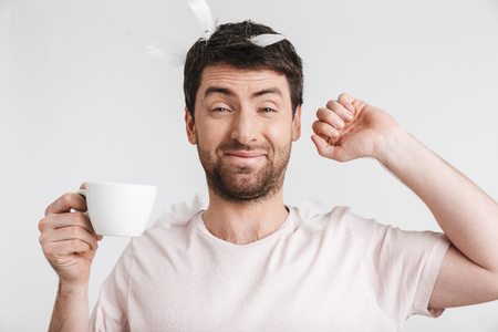 Image of drowsy man 30s with bristle in casual t-shirt drinking coffee while standing under falling feathers isolated over white background