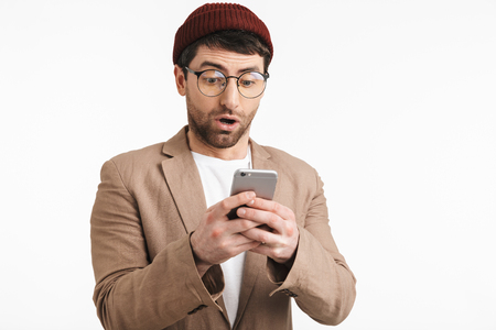 Photo of excited man 30s wearing hipster hat smiling while holding and using smartphone isolated over white background