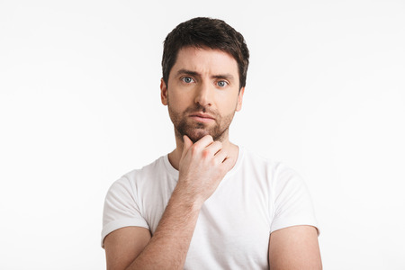 Image of successful man 30s with bristle in casual t-shirt thinking and touching chin isolated over white background Banco de Imagens