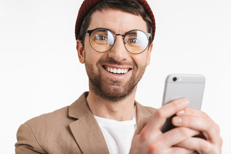Image of attractive man 30s wearing hat and eyeglasses smiling while using smartphone isolated over white background