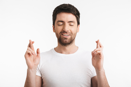Image of optimistic man 30s with bristle in casual t-shirt keeping fingers crossed and making a wish isolated over white background Banco de Imagens