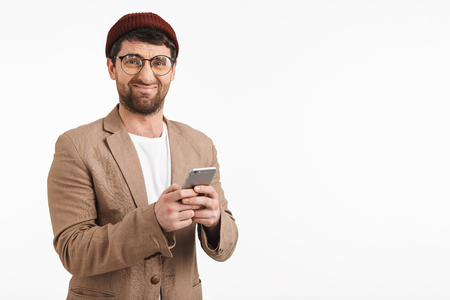 Photo of caucasian man 30s wearing hipster hat smiling while holding and using smartphone isolated over white background