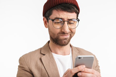 Image of joyful man 30s wearing hat and eyeglasses smiling while using smartphone isolated over white background Stock Photo