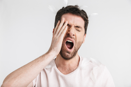 Image of unshaved man 30s with bristle in casual t-shirt yawning while standing under falling feathers isolated over white background