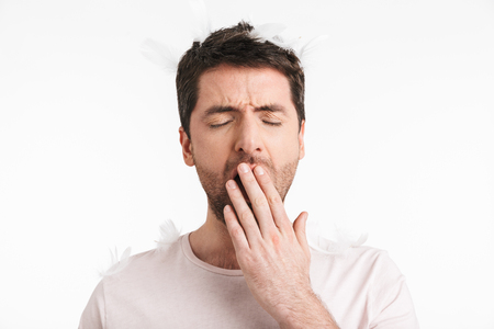 Image of sleepy man 30s with bristle in casual t-shirt yawning while standing under falling feathers isolated over white background