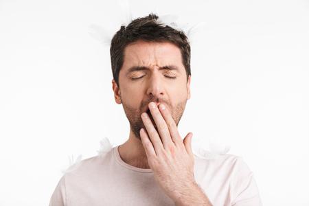 Imagen de hombre soñoliento de 30 años con cerdas en camiseta casual bostezando mientras está de pie bajo las plumas que caen aisladas sobre fondo blanco. Foto de archivo