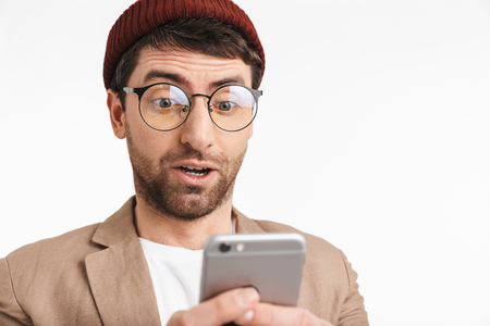 Photo of puzzled man 30s wearing hipster hat smiling while holding and using smartphone isolated over white background