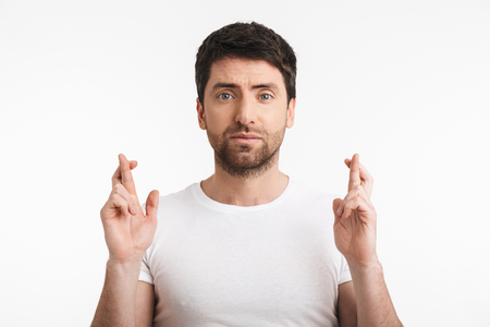 Image of european man 30s with bristle in casual t-shirt keeping fingers crossed and making a wish isolated over white background