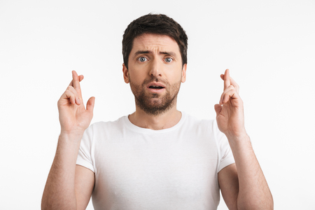 Image of shocked man 30s with bristle in casual t-shirt keeping fingers crossed and making a wish isolated over white background Standard-Bild