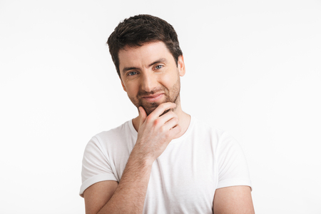 Image of handsome man 30s with bristle in casual t-shirt smiling and touching chin isolated over white background Imagens - 121188678