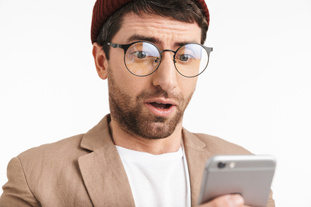 Photo of handsome man 30s wearing hipster hat smiling while holding and using smartphone isolated over white background Stock Photo