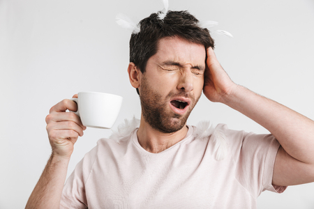 Image of caucasian man 30s with bristle in casual t-shirt drinking coffee while standing under falling feathers isolated over white background Imagens