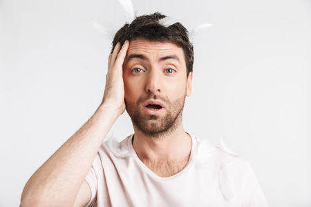 Image of serious man 30s with bristle in casual t-shirt standing under falling feathers isolated over white background