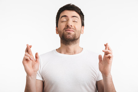 Image of unshaved man 30s with bristle in casual t-shirt keeping fingers crossed and making a wish isolated over white background