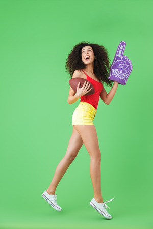 Portrait of delighted woman 20s holding number one fan glove and rugby ball while standing against green wall