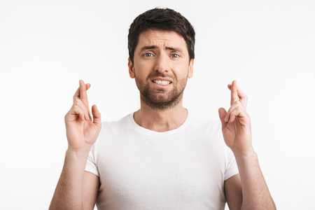 Image of excited man 30s with bristle in casual t-shirt keeping fingers crossed and making a wish isolated over white background Banco de Imagens