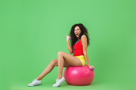 Image of energetic woman 20s wearing summer clothes lifting dumbbells while sitting on fitness ball during aerobics against green wall