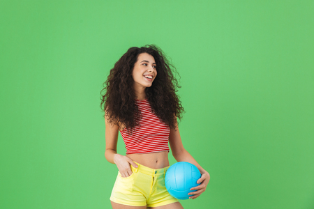 Image of caucasian woman 20s wearing summer clothes smiling and holding volley ball while standing against green background