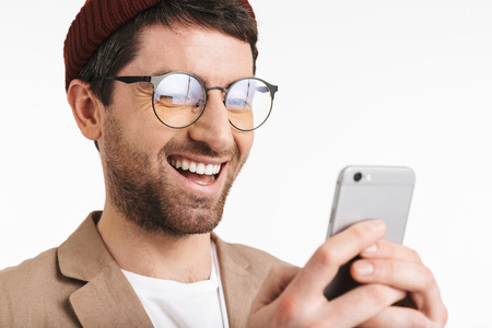 Image of happy man 30s wearing hat and eyeglasses smiling while using smartphone isolated over white background 写真素材