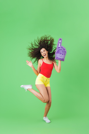 Portrait of european woman 20s rejoicing and holding number one fan glove while standing against green wall Stock Photo