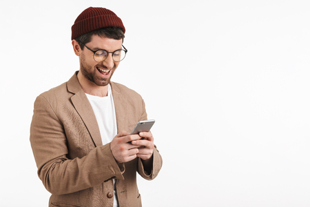 Photo of attractive man 30s wearing hipster hat smiling while holding and using smartphone isolated over white background
