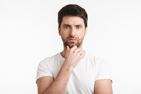 Image of adult man 30s with bristle in casual t-shirt thinking and touching chin isolated over white background