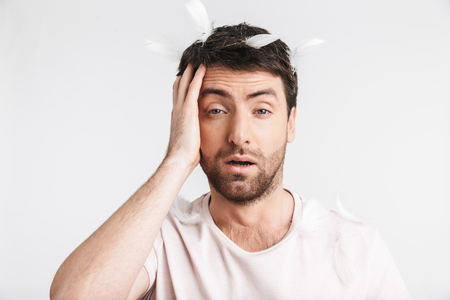 Image of awakened man 30s with bristle in casual t-shirt standing under falling feathers isolated over white background