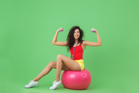 Image of sporty woman 20s wearing summer clothes lifting dumbbells while sitting on fitness ball during aerobics against green wall