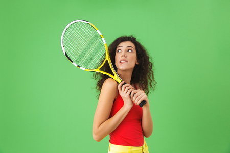 Image of young female tennis player 20s smiling and holding racket while standing against green background