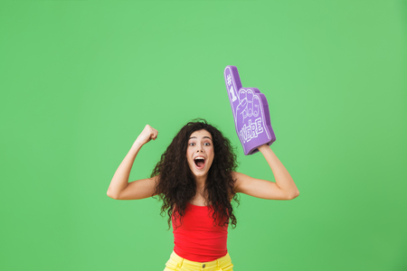 Portrait of modern woman 20s rejoicing and holding number one fan glove while standing against green wall