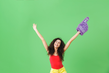 Portrait of attractive woman 20s rejoicing and holding number one fan glove while standing against green wall