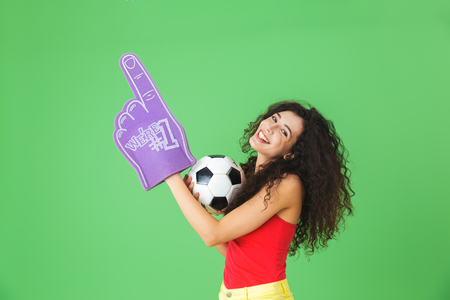 Portrait of caucasian woman 20s holding number one fan glove and soccer ball while standing against green wall